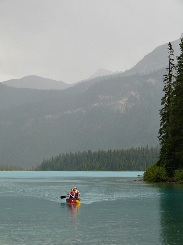 Kayakers in the rain at Emerald Lake in Yoho National Park, Canada - a Rocky Mountain Road Trip must